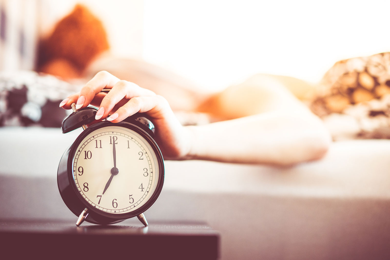 Woman Shutting Off Ringing Alarm Clock From Bed